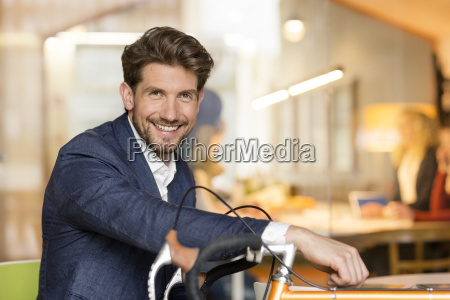 young businessman in office leaning on