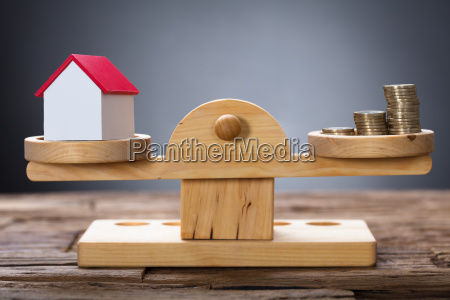 model home and coins balancing on