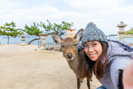 woman taking photo with deer in