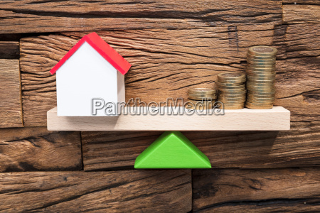 stacked coins and model house balancing