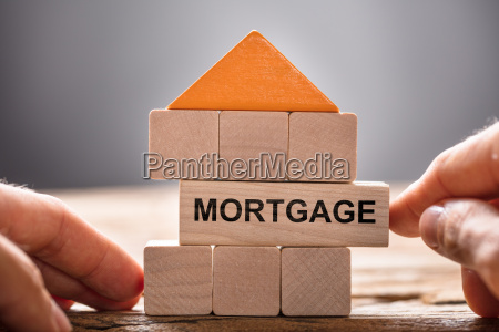 hands building house model with mortgage