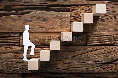 paper businessman climbing block ladder on