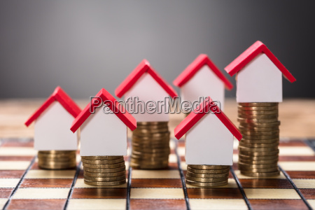 small houses on stacked coins