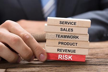 businessman holding red risk block under